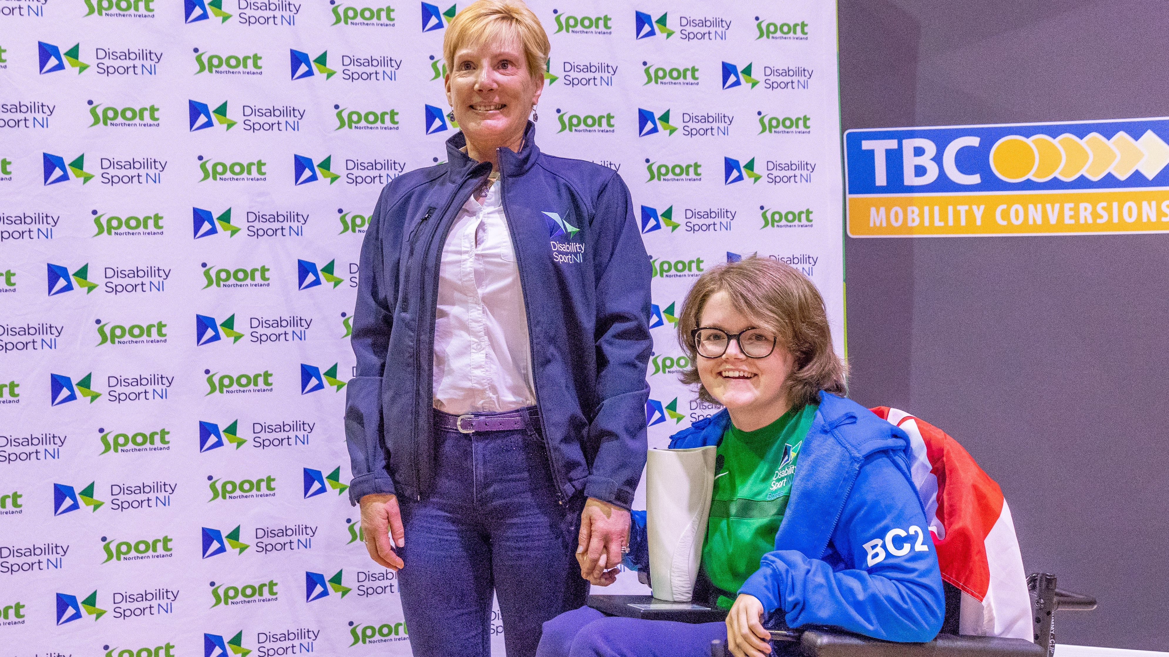 An image of Claire Taggart holding her trophy with Disability Sport NI Honorary President Dr Janet Gray MBE