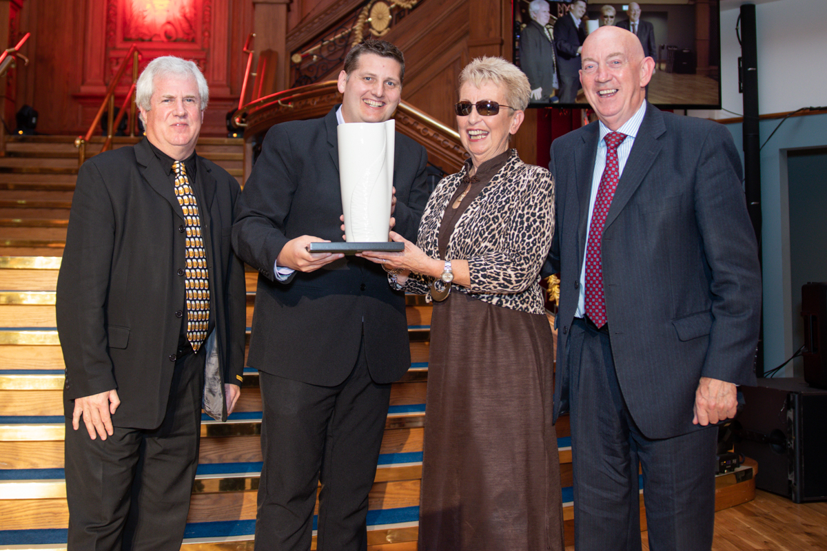 Jan Dinsdale MBE accepting her award from Sport NI's George Lucas and Stuart Robinson from Cool FM