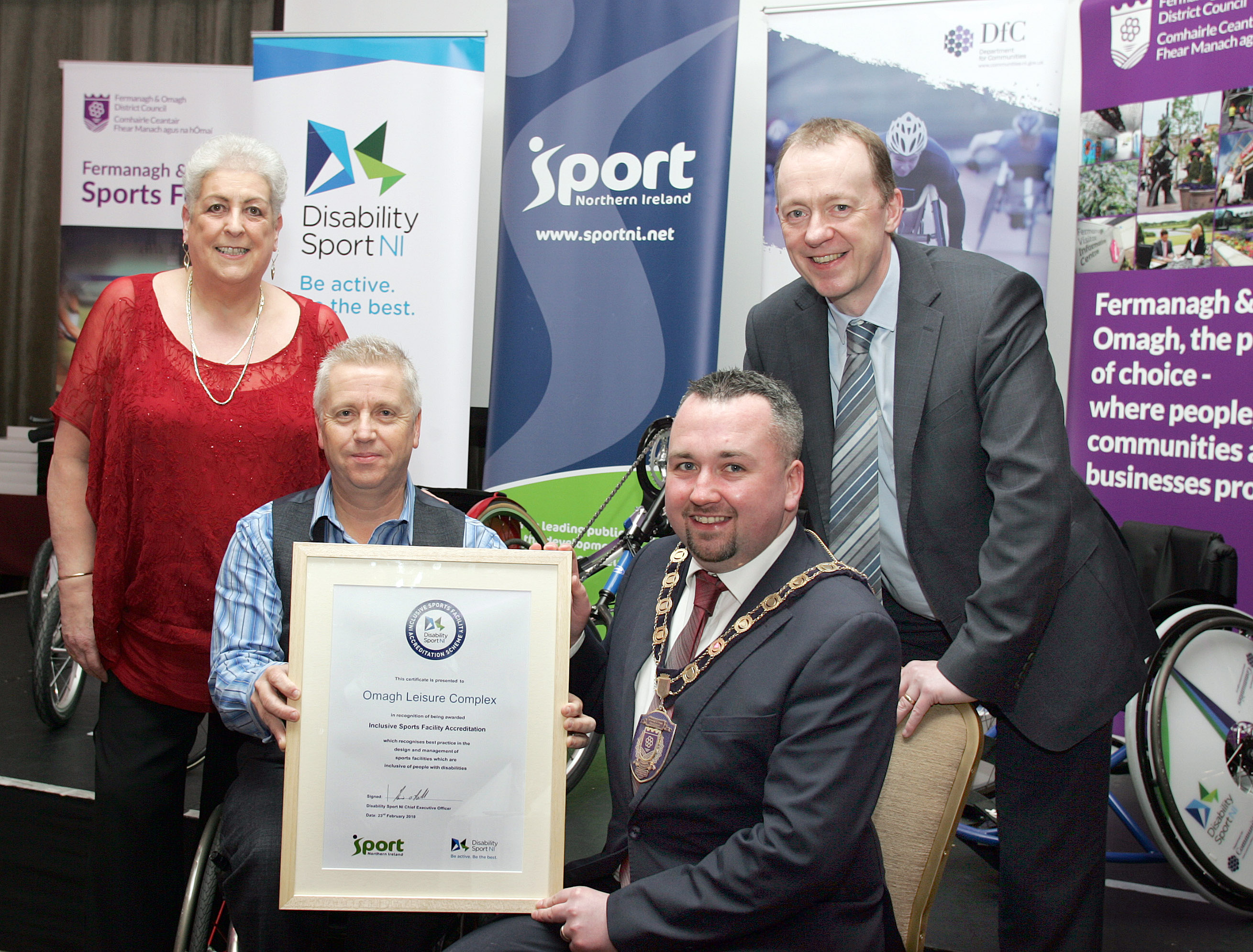 An image of representatives from the councill and Disability Sport NI holding a certificate