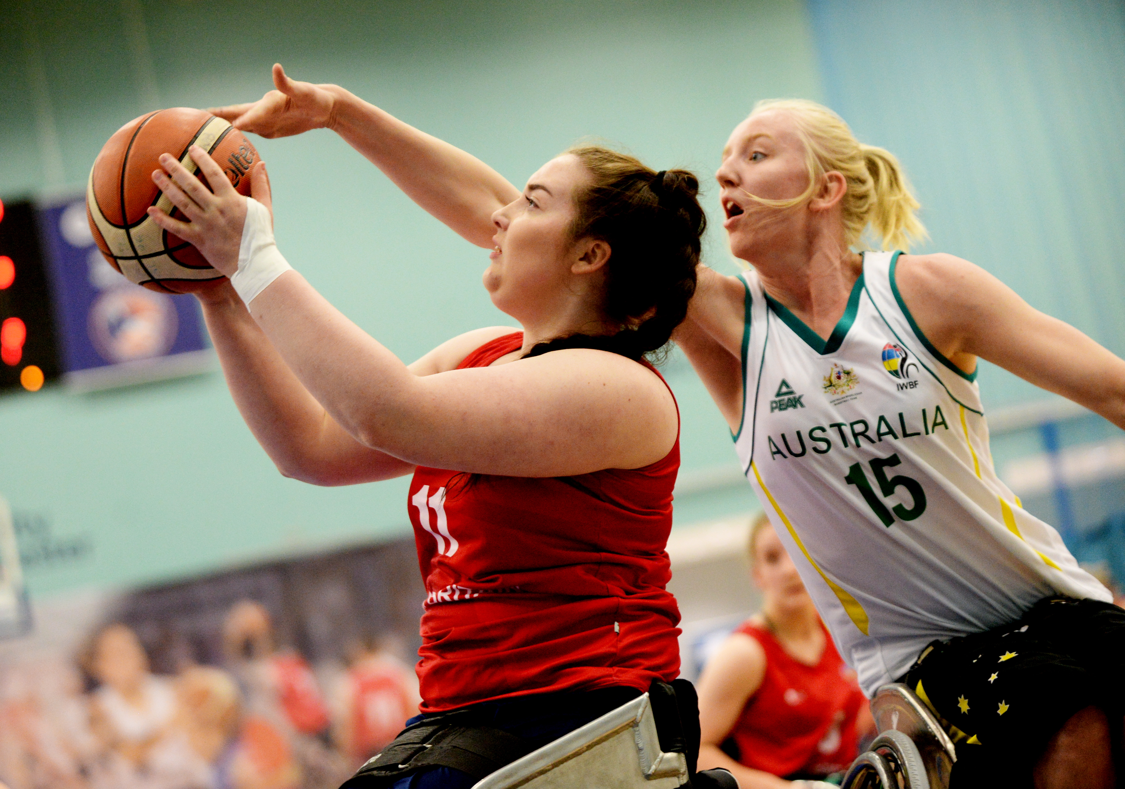 Photo of Katie Morrow playing wheelchair basketball. Katie is taking a shot and someone is going in to try and block her.