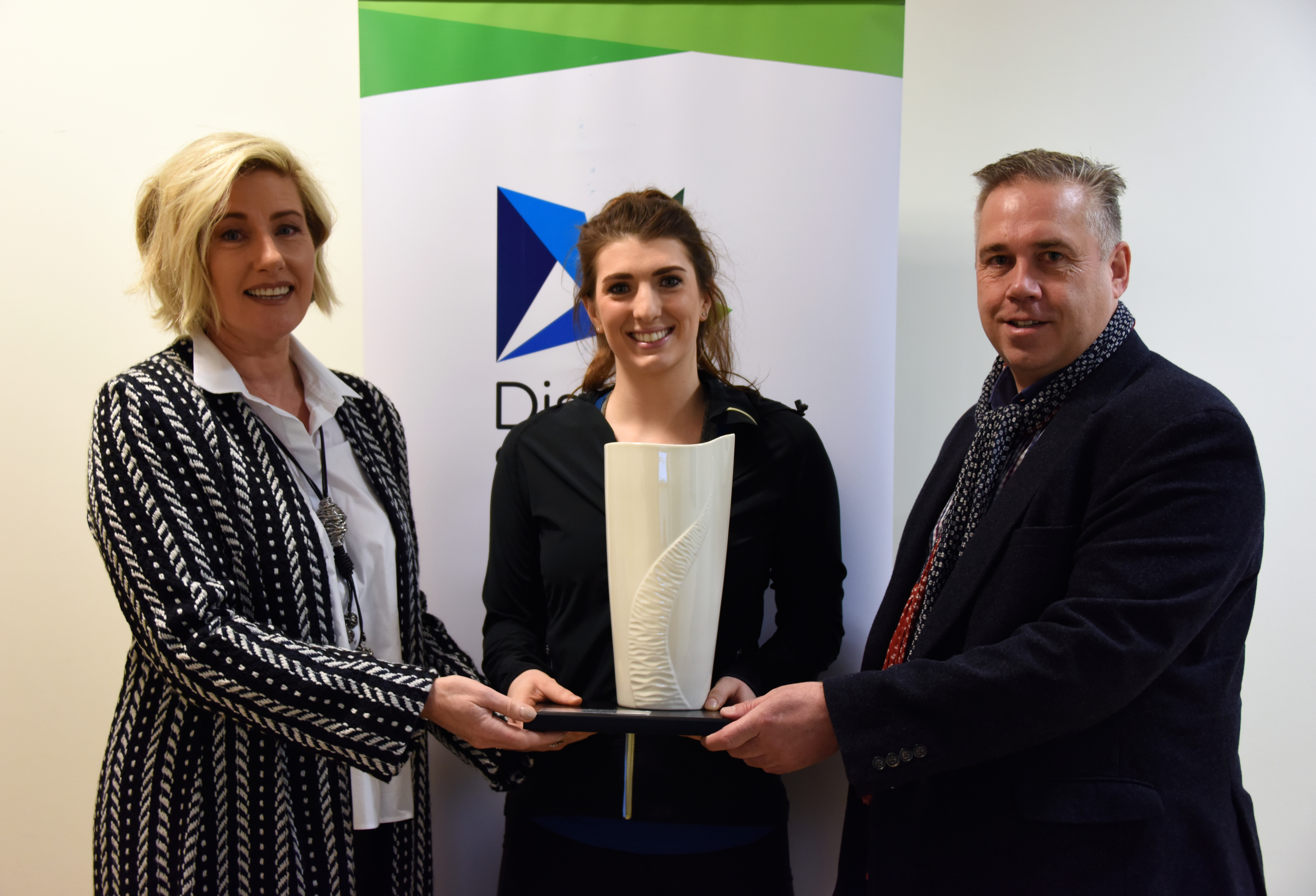 An Image of Bethany Firth MBE at SINI receiving her award from Brian and Sharon McFarland from McFarland Associates