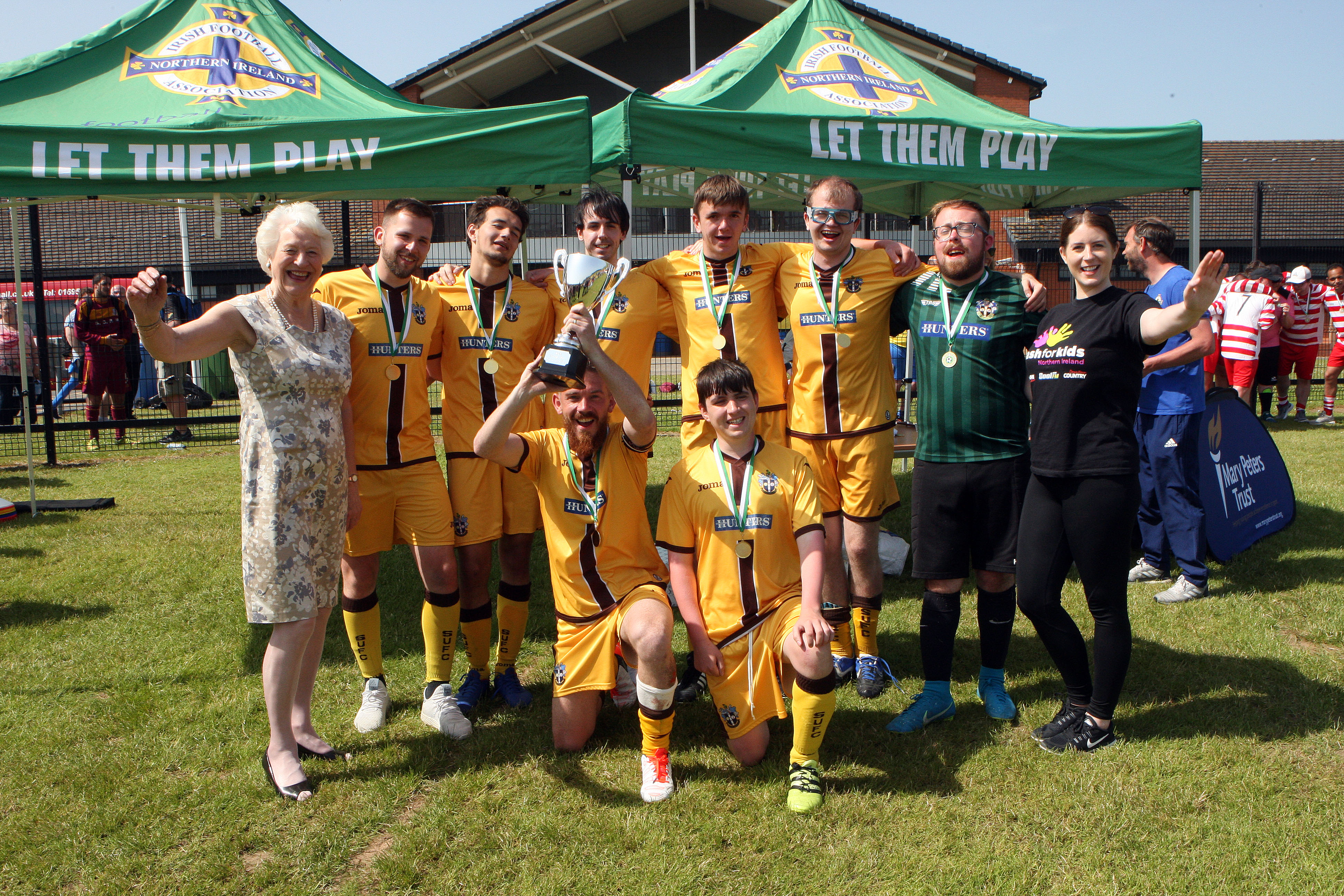 An image of a number of footballers holding a cup with Dame Mary Peters