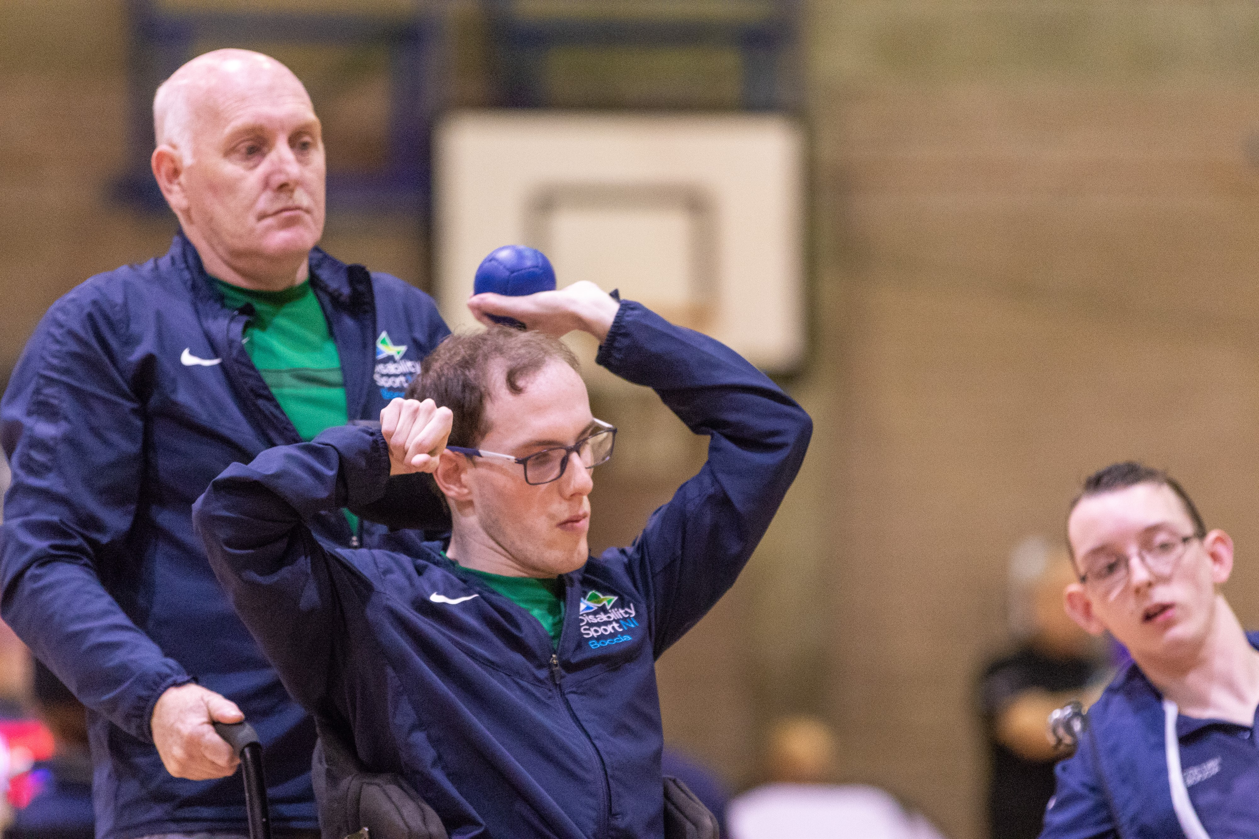 An image of William Graham about to throw the Boccia Ball with his father Joe behind him