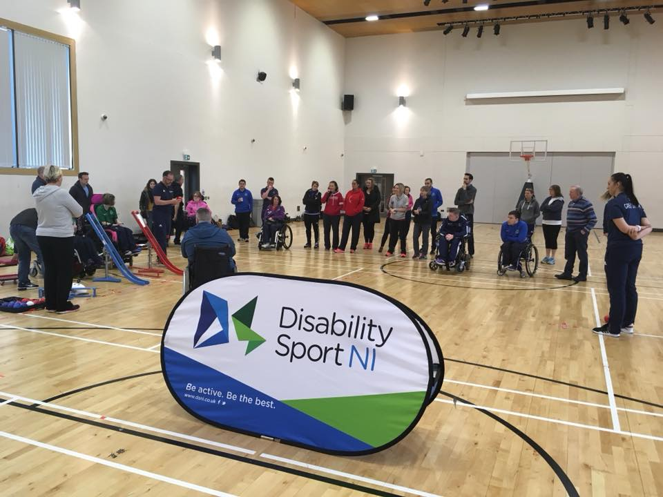 A group image of people gathered in a sports hall tryign new boccia techniques