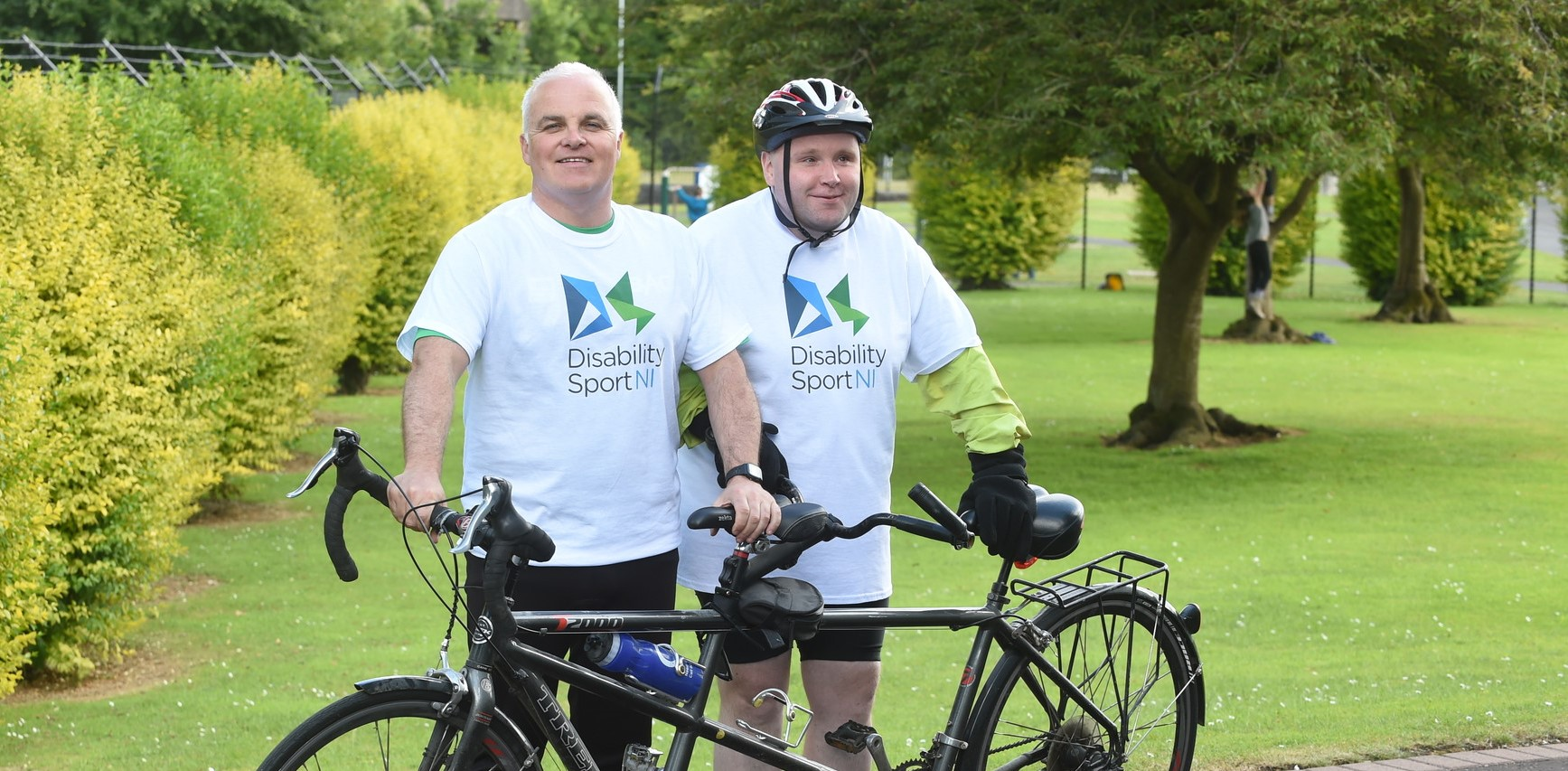 An image of Barry and Thomas standing with a tandem bike.