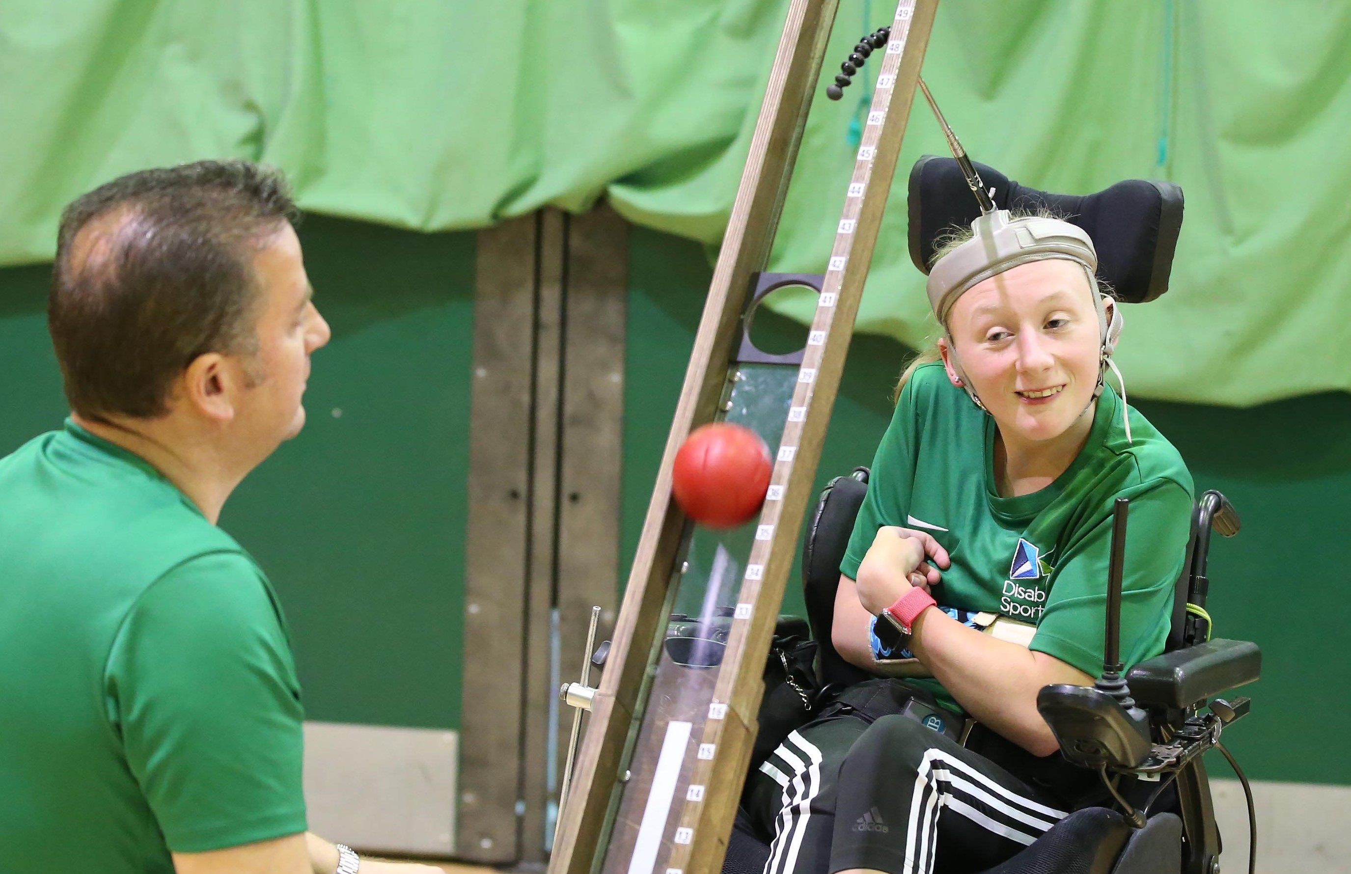 An image of Robyn pushing the ball with her father Davey in front of her as her ramp assistant