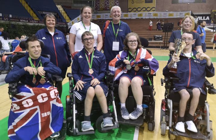 An image  of Claire with her team mates, coaches and her father with her Bronze medal