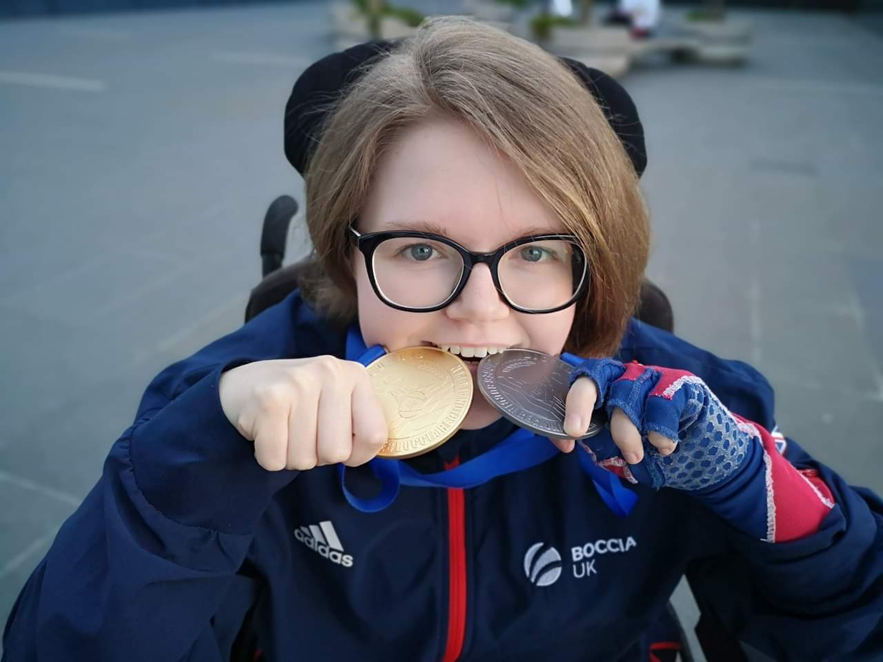Claire Taggart holding Silver and Gold medals in her mouth.