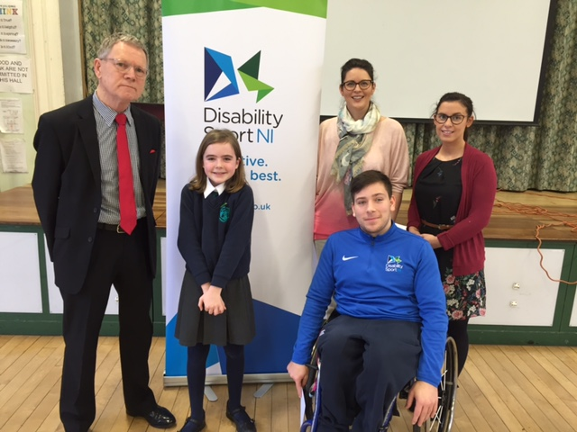 Andrea Herron and Luke Marshall from Disability Sport NI with representatives from Strandtown Primary School standing in front of a Disability Sport NI banner