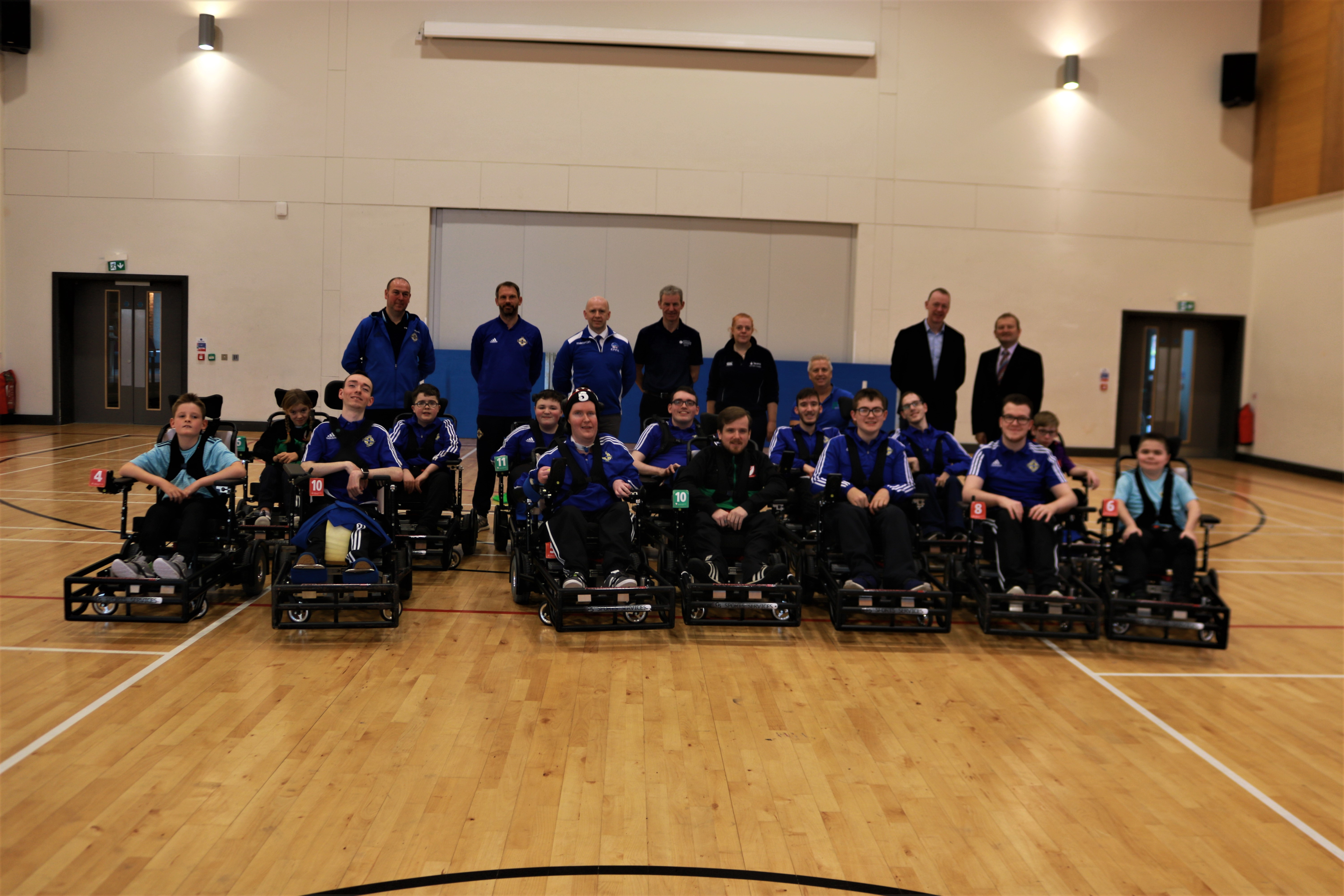 An image of the NI Powerchair Football Team with key funding representatives from Sport NI, Department for Communities and Disability Sport NI as well as the IFA.
