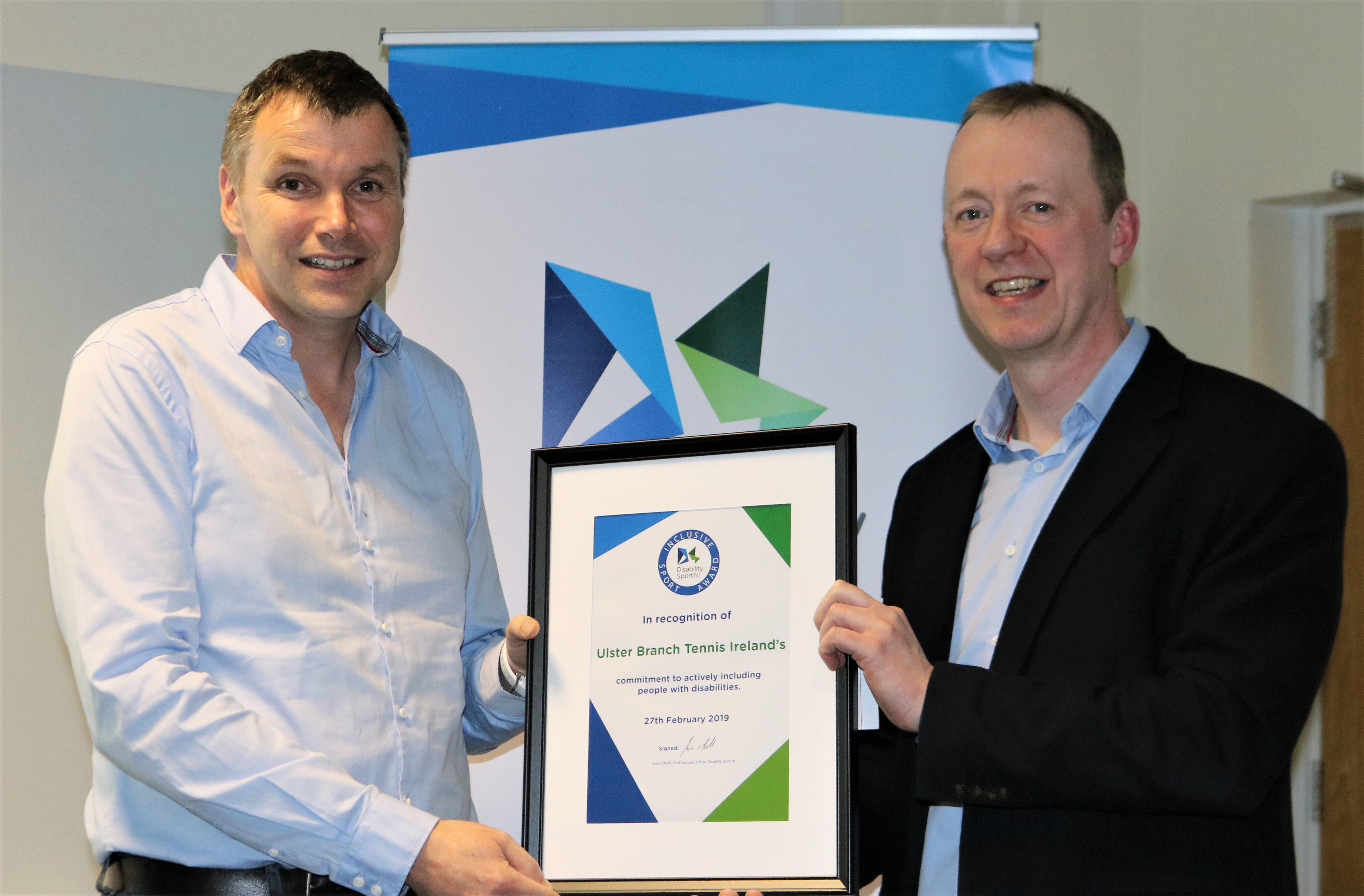An image of two people holding a certificate.