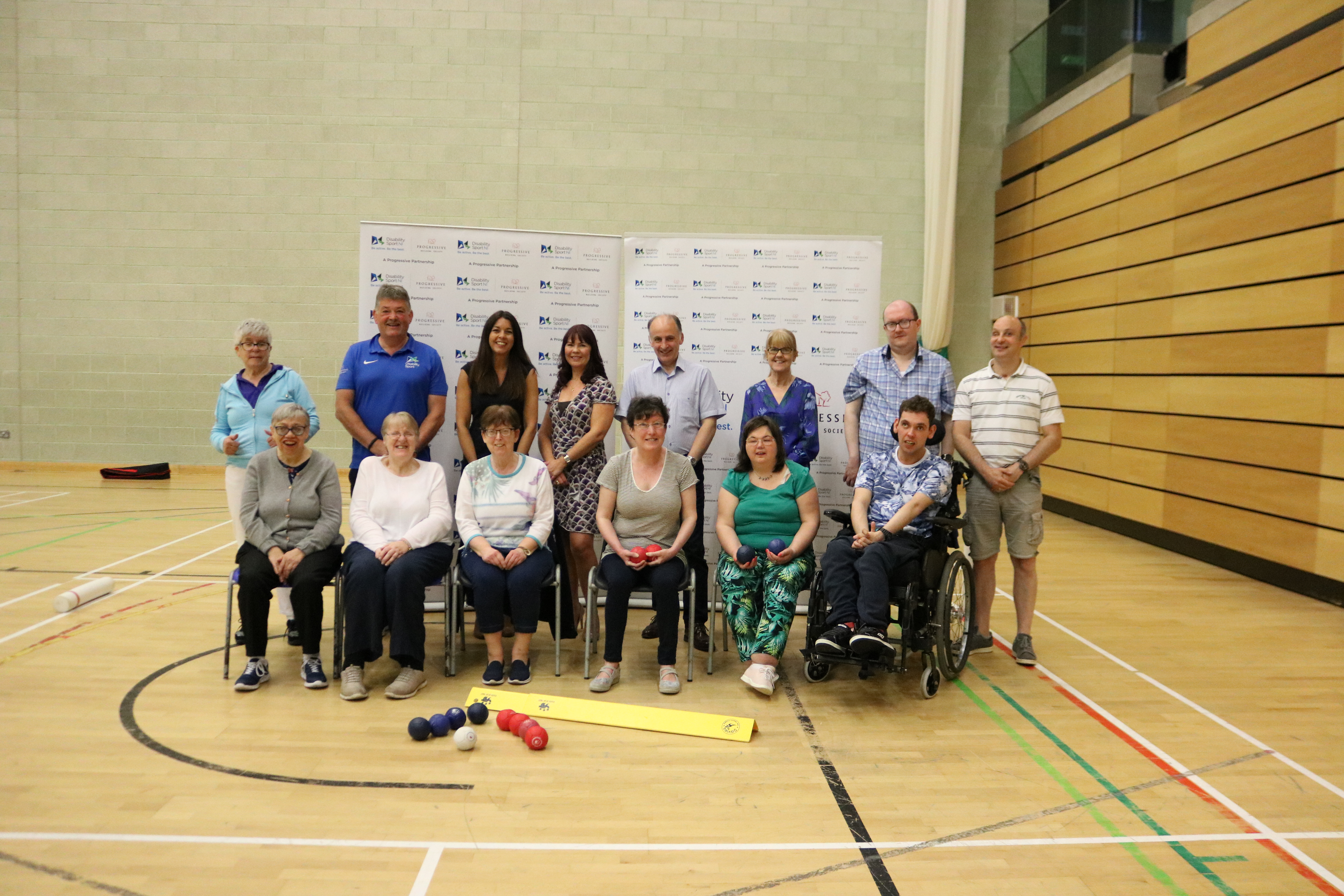 An image of a boccia group sitting posing for the camera with representatives from Disability Sport NI and The Progressive Building Society