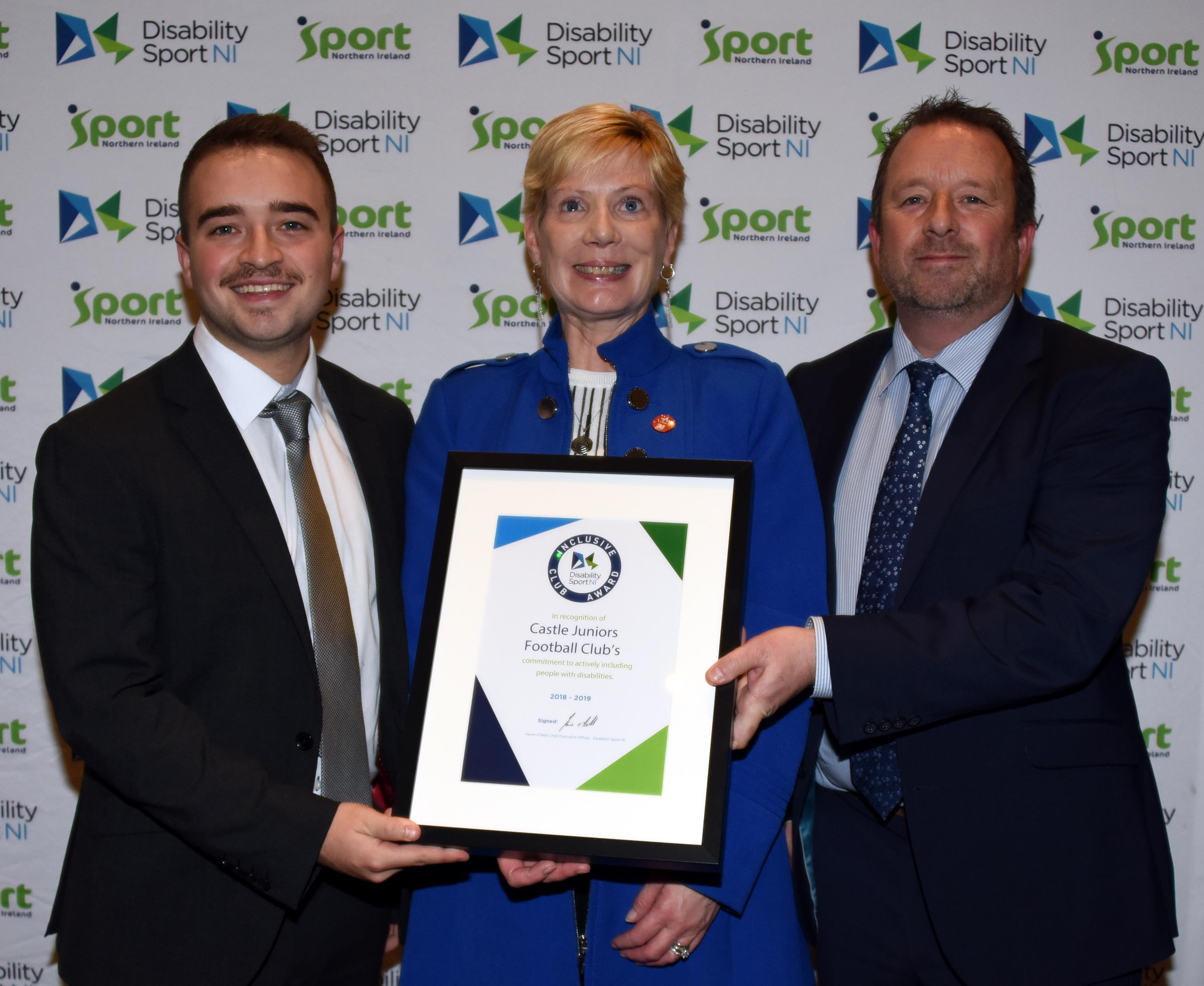 An image of Dr Janet Gray MBE presenting the certificate to Robbie Ried and Trevor Reid from Castle Juniors Football Club