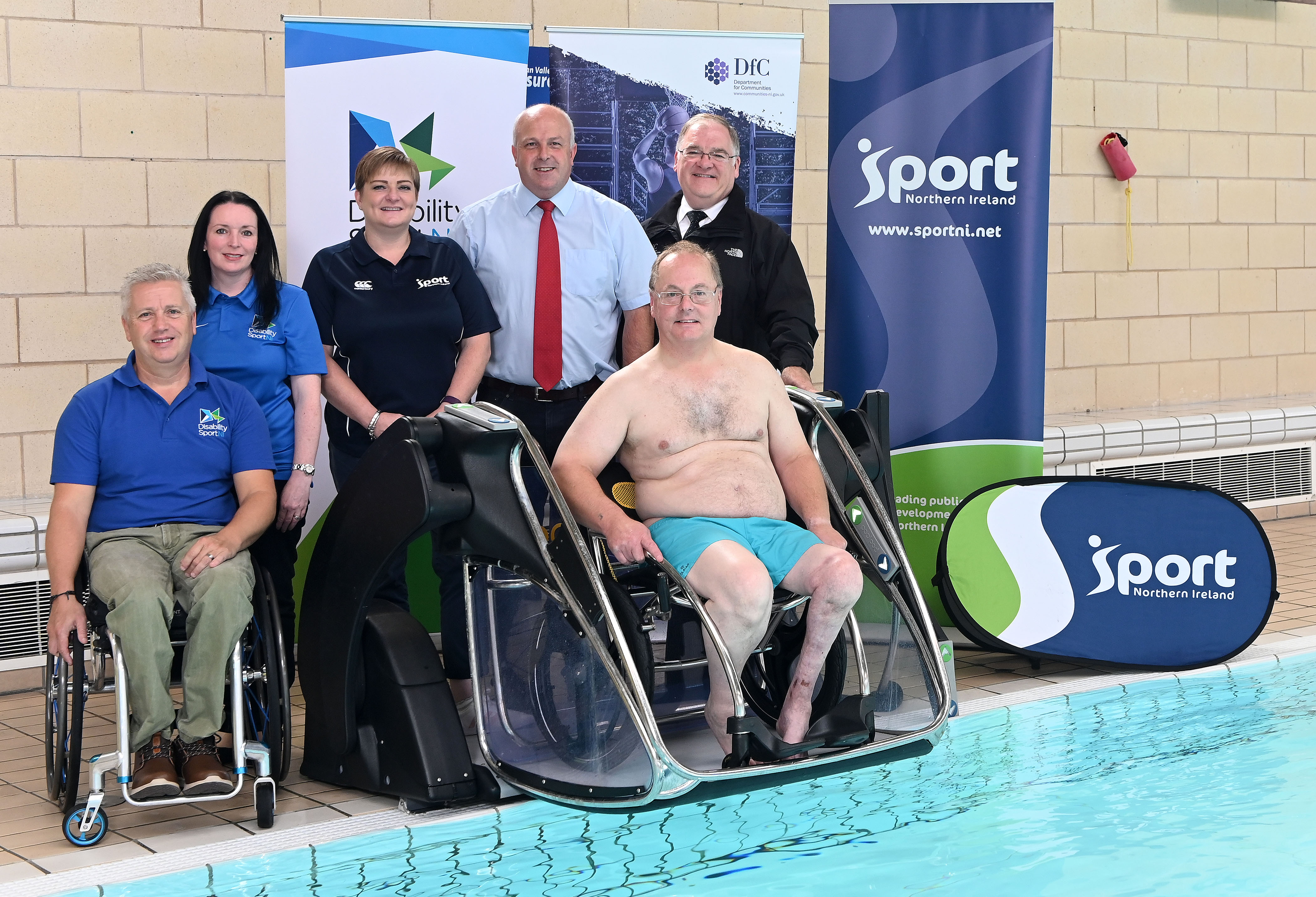 An image of representatives from the council, Sport NI and Department for Communities at the Poolpod with a pool user.