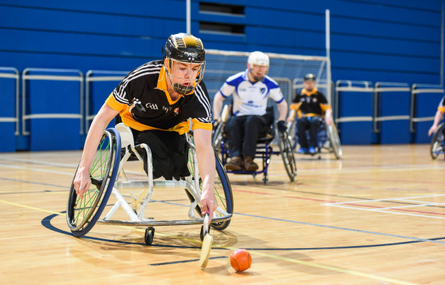 An image of people playing wheelchair hurling on court