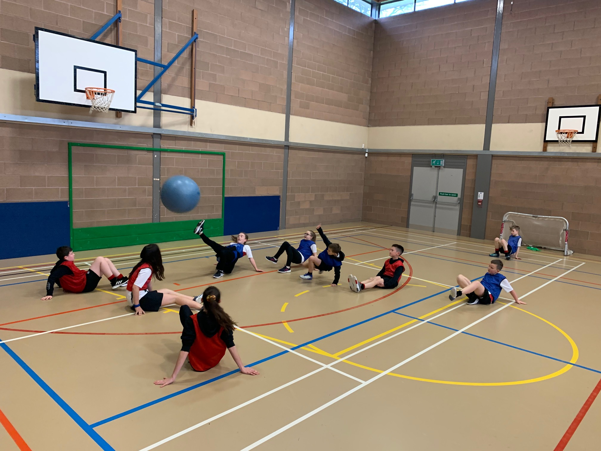 A group of children in a school gym playing crab football