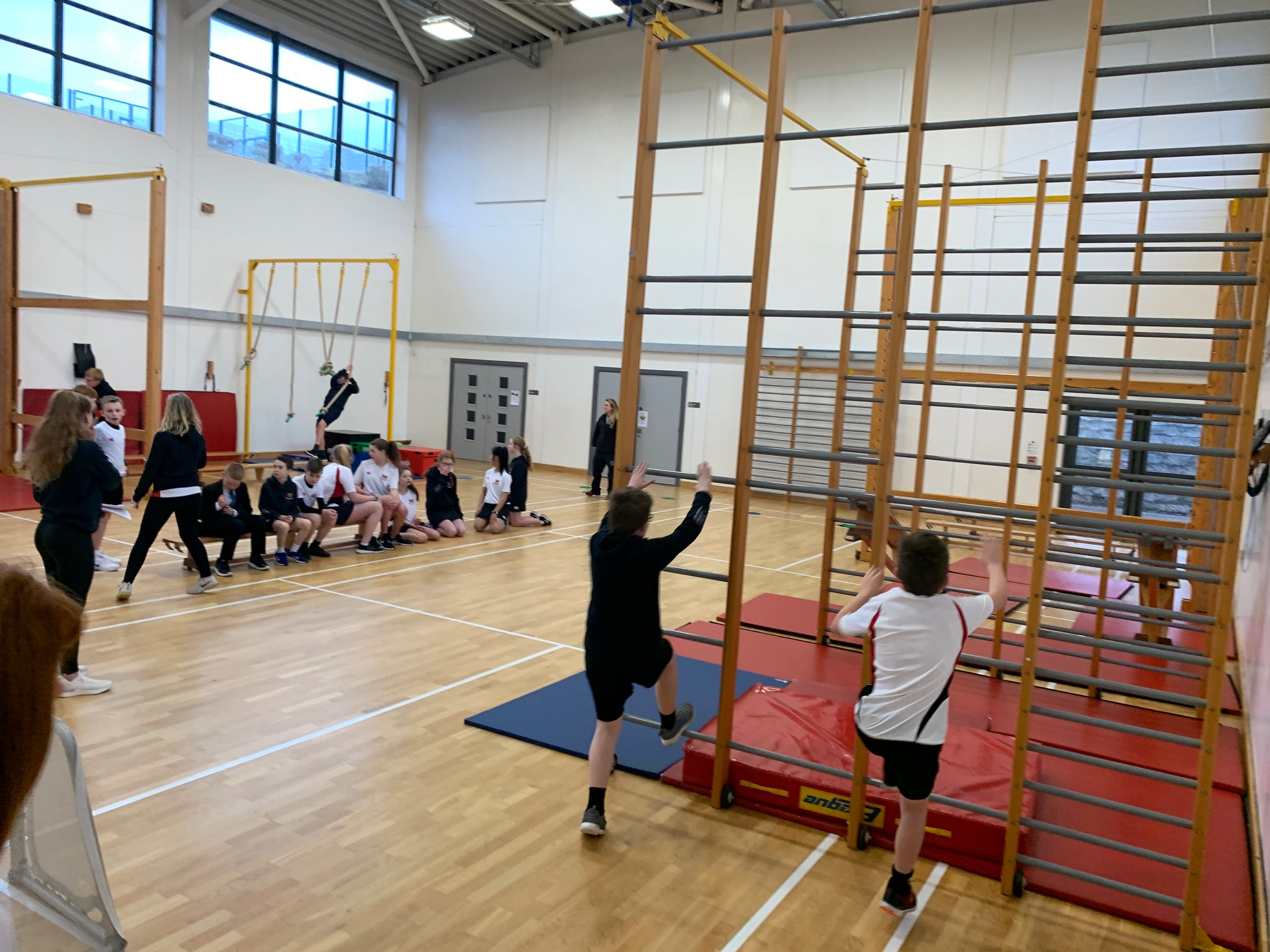 People in a school gym climbing up the apparatus