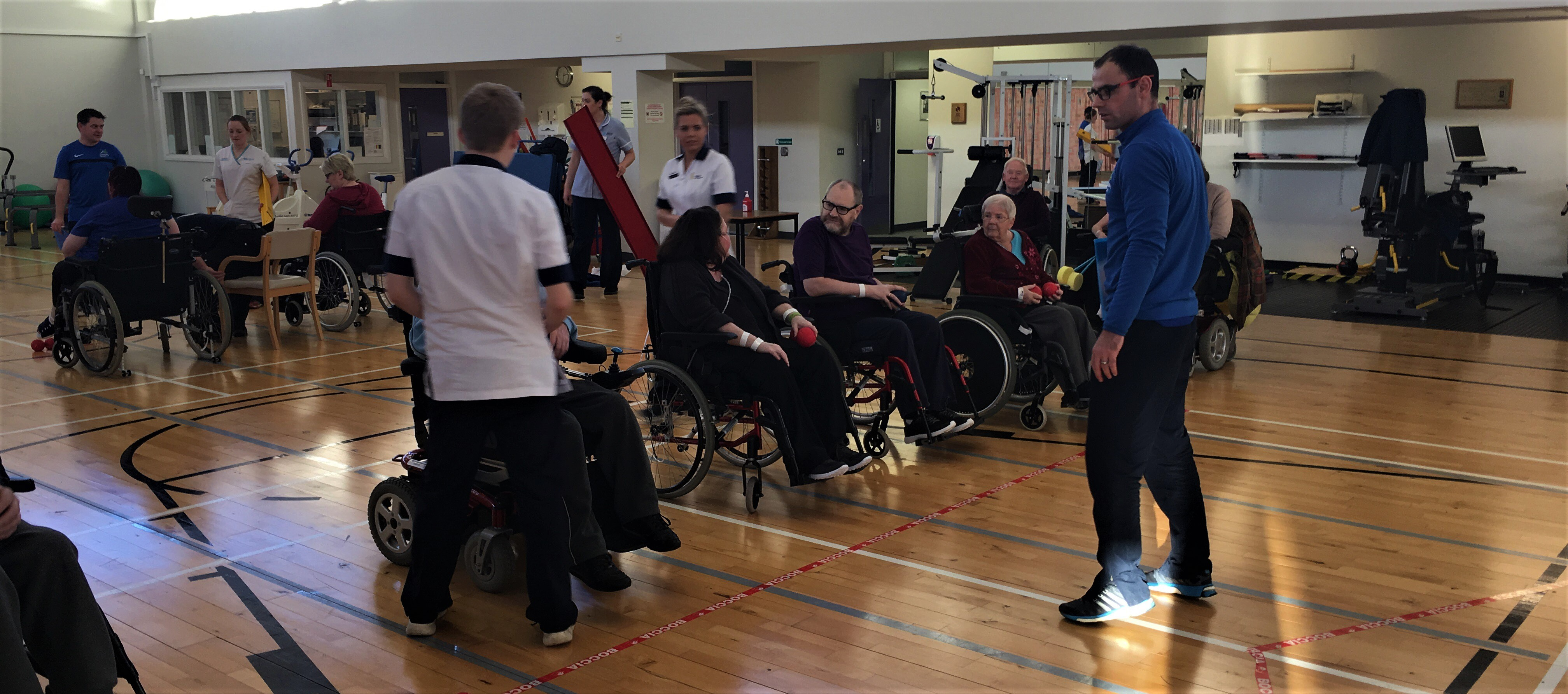 A group of people lined up to play boccia
