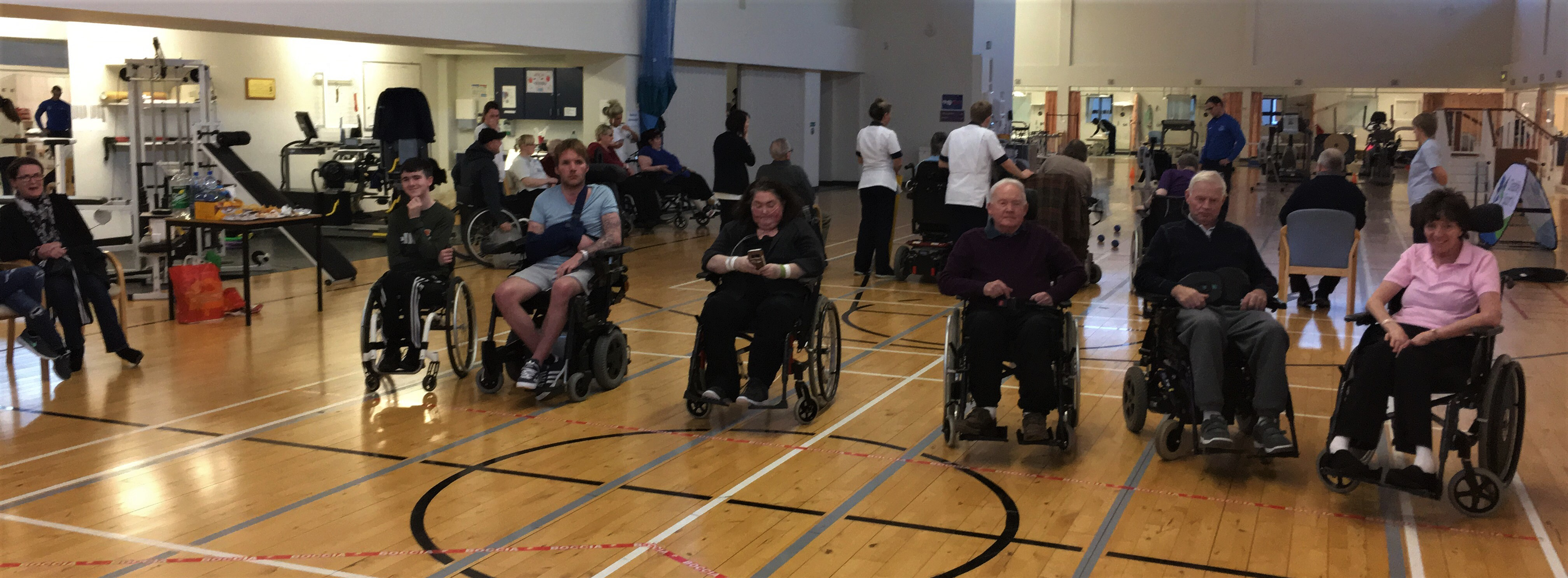 A group of people who are wheelchair users lined up to play boccia