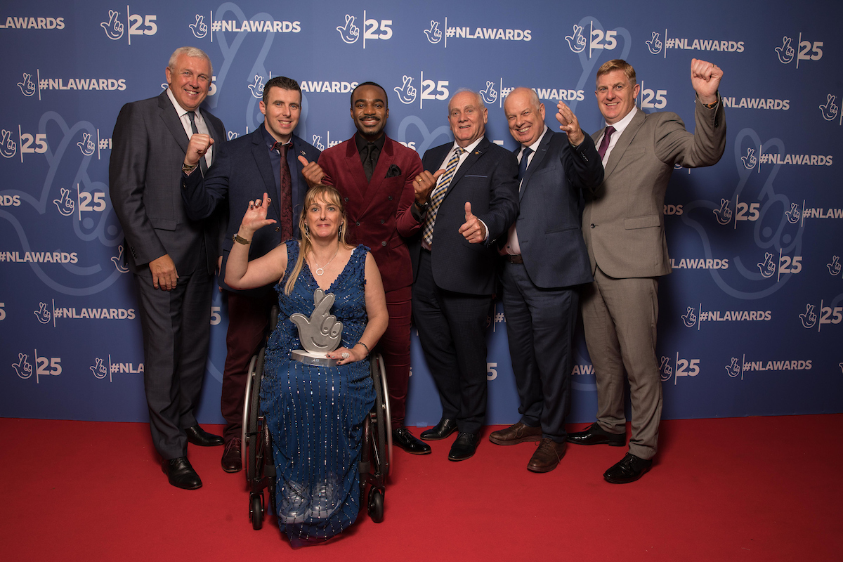An image of the wheelchair hurling team with sporting legends team after their award presentation